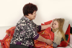 Woman taking care of a sick daughter. Woman taking care of a sick teenage daughter Stock Photos