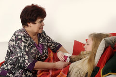 Woman taking care of a sick daughter. Woman taking care of a sick teenage daughter Stock Image
