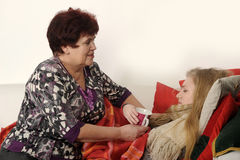 Woman taking care of a sick daughter. Woman taking care of a sick teenage daughter Royalty Free Stock Photography
