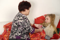 Woman taking care of a sick daughter. Woman taking care of a sick teenage daughter Royalty Free Stock Image