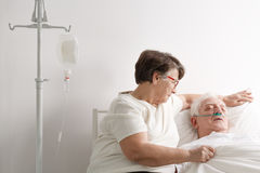Woman taking care of sick husband. Senior women taking care of her sick husband in hospice stock photos