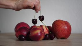 Woman taking cherries from the table. Slow motion video woman taking cherries from the wood table stock video