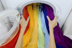 Woman taking color  clothes from washing machine Royalty Free Stock Photo