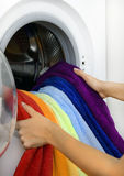 Woman taking color laundry from washing machine Stock Photo