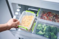 Woman taking container with frozen corn   refrigerator. Woman taking container with frozen corn from refrigerator Stock Photos