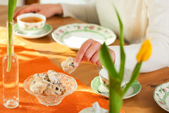 Woman taking cookies from coffee table Stock Image