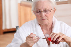Woman taking cough syrup. Senior woman taking cough syrup Royalty Free Stock Photography
