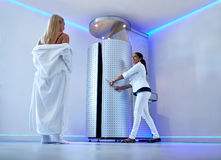Woman taking cryosauna treatment at cosmetology clinic. Full length portrait of women in bathrobe at cosmetology clinic going for cryotherapy treatment in Stock Photography
