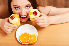 Woman taking delicious sweet cake. Gluttony. Stock Photo