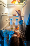 Woman taking donut from top shelf of refrigerator Royalty Free Stock Photos