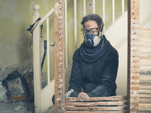 Woman taking down wattle and daub wall. A young woman wearing protective goggles and a dust mask is using a hammer to demolish an old wattle and daub wall Stock Images