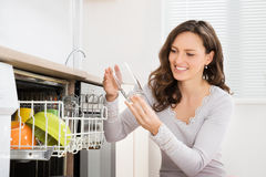 Woman Taking Drinking Glass From Dishwasher Stock Photos