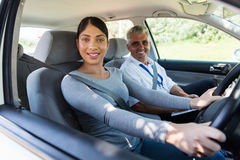 Woman taking driving lessons. Beautiful young women taking driving lessons royalty free stock photo