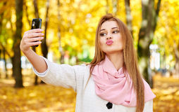 Woman taking duckface selfie in autumn city park Royalty Free Stock Photos
