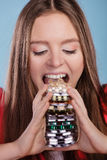 Woman taking eating pills tablets. Drug addict. Woman taking pills. Girl female eating stack of tablets. Drug addict and health care concept. Overdose Royalty Free Stock Photography