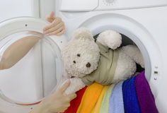 Woman taking fluffy toy from washing machine Stock Photography