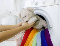 Woman taking fluffy toy from washing machine Stock Photos