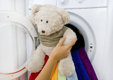 Woman taking fluffy toy from washing machine Royalty Free Stock Images