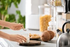 Woman taking fresh coconut oil from glass jar. On table in kitchen. Healthy cooking stock image