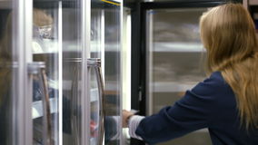 Woman taking frozen product from the fridge in the stock footage