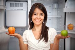 Woman taking fruits from the fridge Stock Photos