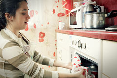 Woman taking frying pan from oven Royalty Free Stock Photos