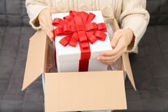 Woman taking gift box out of parcel. At home Royalty Free Stock Photography