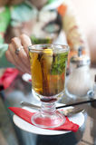 Woman taking a glass of  herbal tea Stock Image