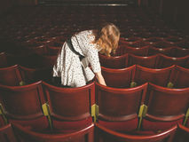 Woman taking her seat in auditorium Royalty Free Stock Photography