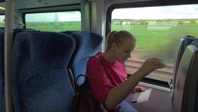 Woman taking her seat in the train. Young woman looking for a seat in train carriage. She taking it according to the ticket and starting work with tablet stock video footage