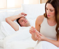 Woman taking her sick husband's temperature Stock Photo