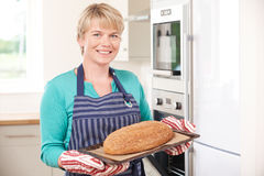 Woman Taking Home Baked Loaf Out Of Oven Stock Photo
