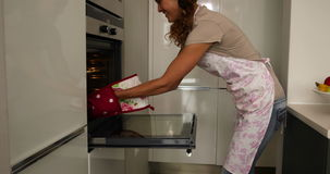 Woman taking hot cookies out of the oven Royalty Free Stock Photo