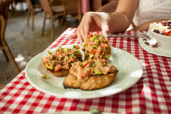 Woman taking italian bruschetta from plate Royalty Free Stock Photography