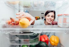 Woman taking a lemon out of the fridge. Smiling woman taking a fresh lemon out of the fridge, healthy food concept stock photography