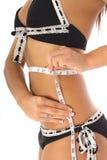 Woman taking measurements in a bikini Stock Images