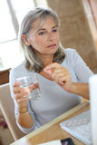 Woman taking medicament with help of internet Stock Photo