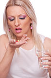 Woman taking medication Stock Photography