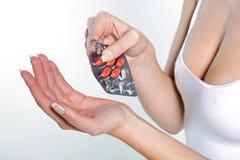 Woman taking medicine pils tablets Stock Photo
