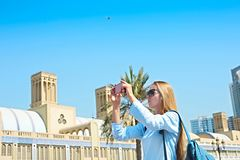 Woman taking mobile photo of the Central Souq in Sharjah City, U. Woman taking mobile photo of the Central Souq market in Sharjah City, United Arab Emirates stock photo
