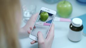 Woman taking mobie photo of positive pregnacy test. Pregnancy concept stock footage