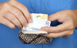 Woman taking money out of her purse. Royalty Free Stock Image