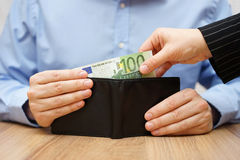 Woman is taking money out of a husband's wallet Royalty Free Stock Images