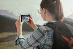 Woman taking nature pictures with her phone Stock Images