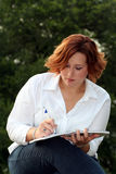 Woman taking notes. Taking notes royalty free stock image