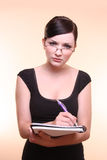 Woman taking notes. Young woman looks attentive as she takes notes in front of a peach background Royalty Free Stock Image
