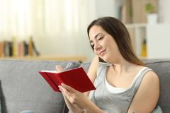 Woman taking notes in agenda during a phone call. Sitting on a couch in the living room at home Stock Photography