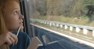 Woman taking notes or drawing in train stock footage