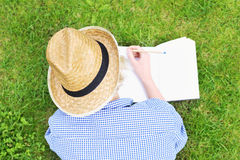 Woman taking notes on grass Stock Photography