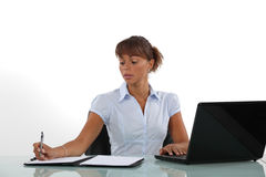 Woman taking notes. At her desk Stock Images